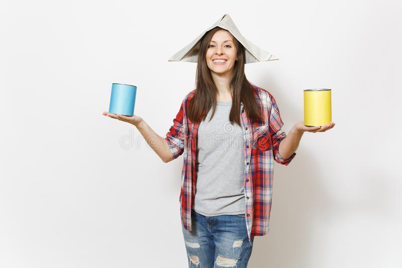 Mulher bonita de sorriso nova na roupa ocasional e no chapéu do jornal que mantém latas de lata da pintura isoladas no fundo bran imagem de stock royalty free