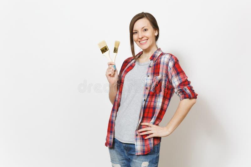 Mulher bonita de sorriso nova na roupa ocasional que mantém escovas de pintura isoladas no fundo branco Instrumentos fotos de stock royalty free