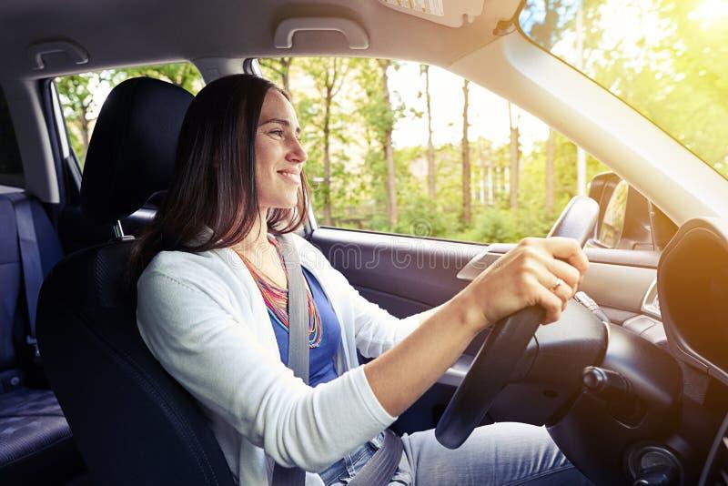 Mulher bonita de sorriso que conduz um carro com o cinto de segurança prendido foto de stock