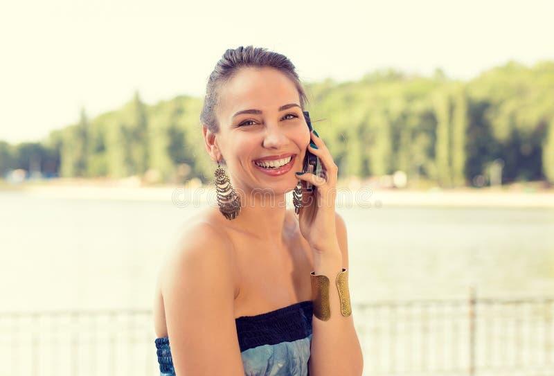 Mulher bonita de sorriso que fala no telefone celular fora pelo lago fotografia de stock