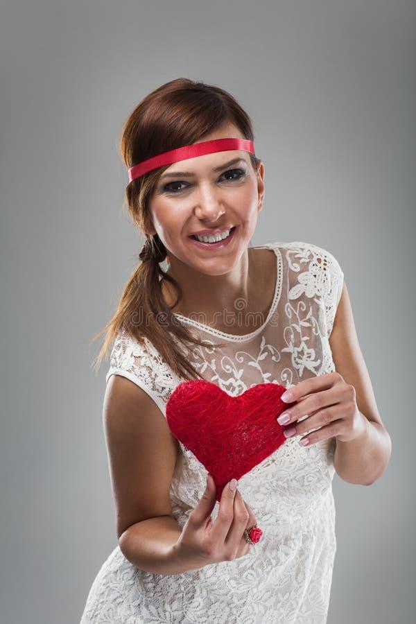 Mulher bonita de sorriso que guarda o coração vermelho imagens de stock royalty free