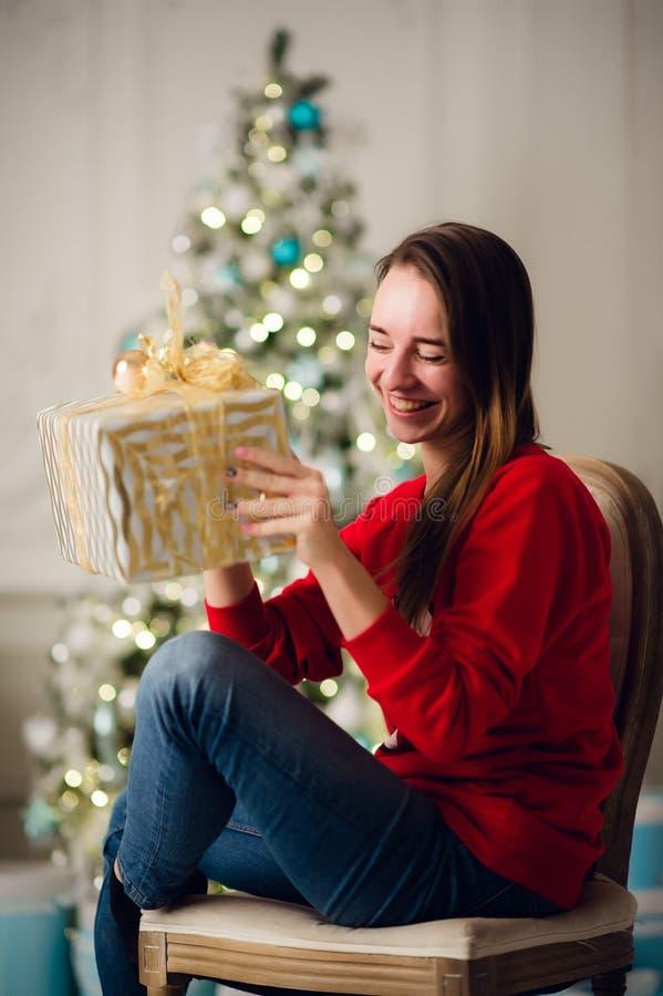 Mulher bonita de sorriso que senta-se sobre a árvore de Natal no fundo imagem de stock