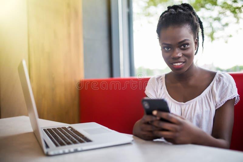 Mulher bonita de sorriso que usa o telefone celular ao sentar-se no café Mulher afro-americano nova que senta-se em uma cafetaria fotografia de stock