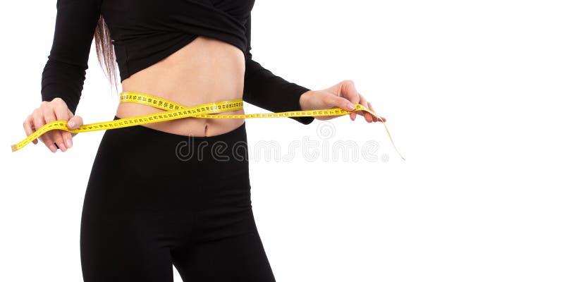 Mulher bonita de terno preto isolada sobre fundo branco Feche o esportivo e lindo corpo feminino Mulher com fita métrica foto de stock