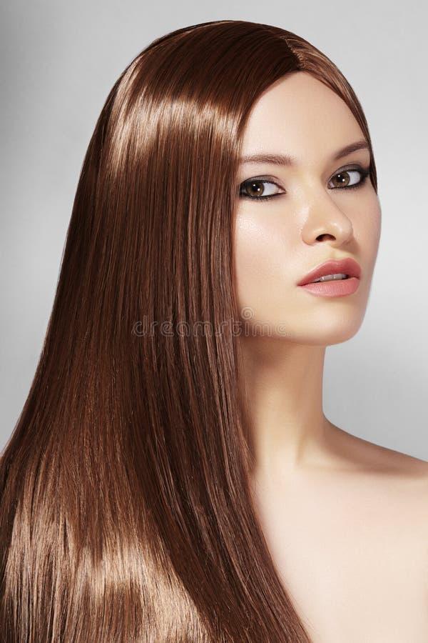 Mulher bonita de Yong com cabelo marrom por muito tempo reto Modelo de forma 'sexy' com penteado liso do brilho Tratamento de Ker foto de stock