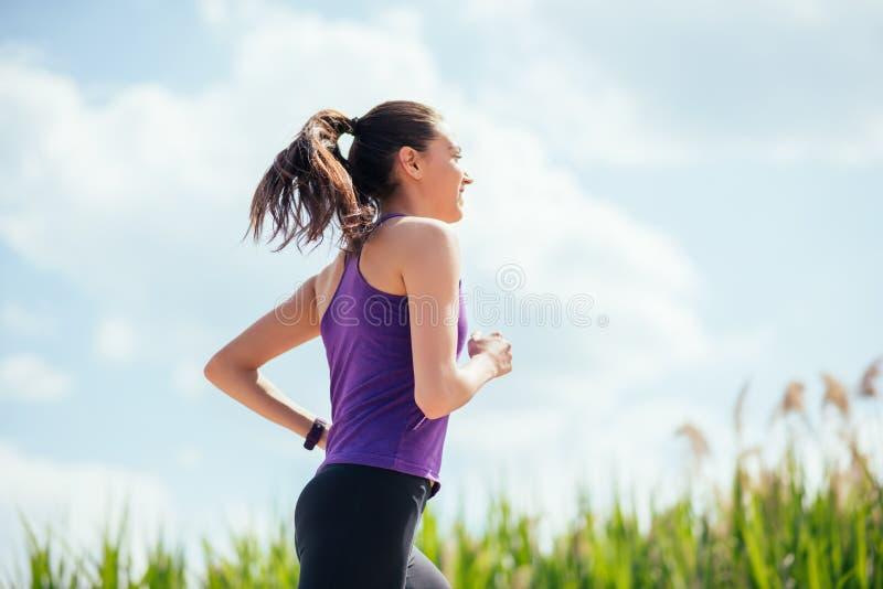 Mulher bonita desportiva que corre no parque no fundo da natureza Dia ensolarado, exercício duro imagem de stock