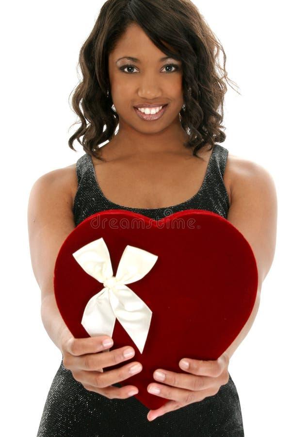Mulher bonita do americano africano com a caixa dos doces do coração de veludo