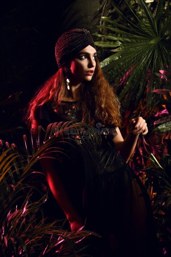 Mulher bonita do cabelo encaracolado da forma que levanta no vestido verde na floresta tropical das folhas foto de stock royalty free