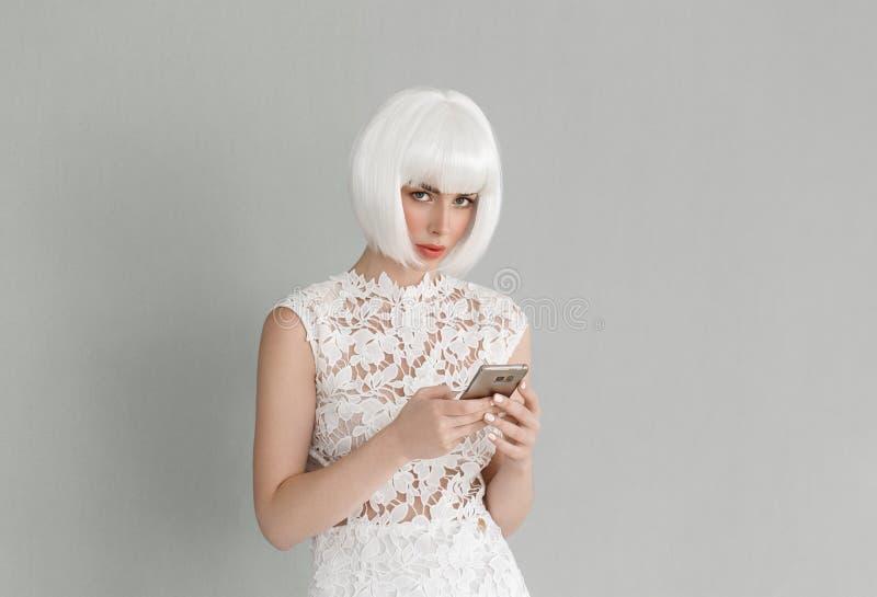 Mulher bonita do cabelo louro com telefone celular no vestido branco nat foto de stock royalty free