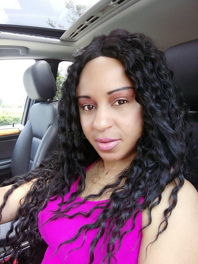 Mulher bonita do cabelo ondulado na fotografia do encanto do carro fotos de stock
