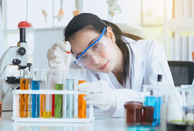 A mulher bonita do cientista que trabalha e que põe a amostra médica dos produtos químicos no tubo de ensaio no escritório do lab foto de stock royalty free