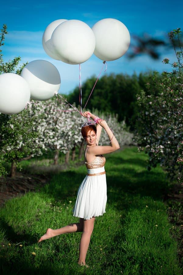Mulher bonita do divertimento que guarda os balões brancos do hélio, imagem de stock
