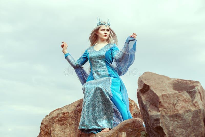A mulher bonita do duende senta-se em uma pedra fotografia de stock royalty free