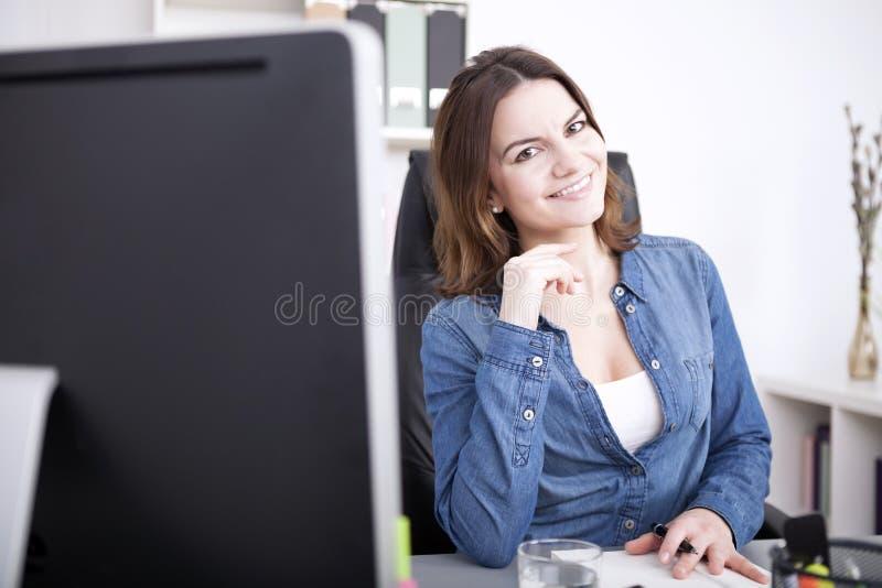Mulher bonita do escritório que sorri em seu Worktable fotografia de stock royalty free