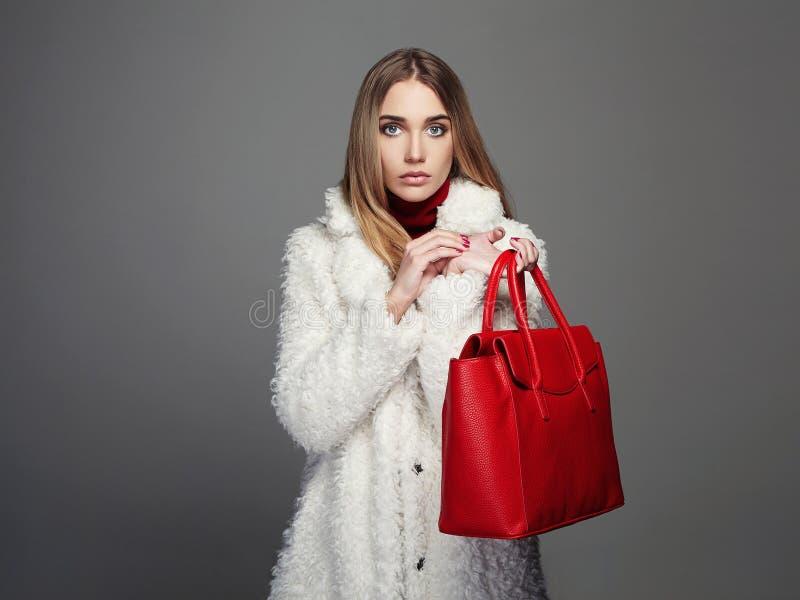 Mulher bonita do inverno com bolsa vermelha Modelo de forma Girl da beleza na pele foto de stock royalty free