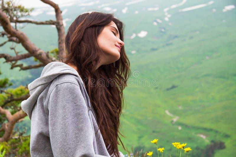 Mulher bonita do moderno do retrato que senta-se na parte superior da montanha fotografia de stock