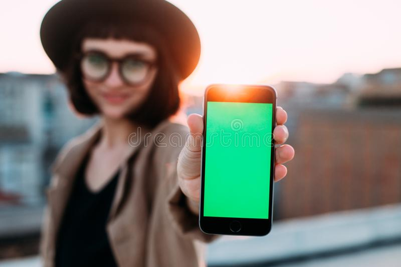 A mulher bonita do moderno guarda o smartphone à câmera imagem de stock