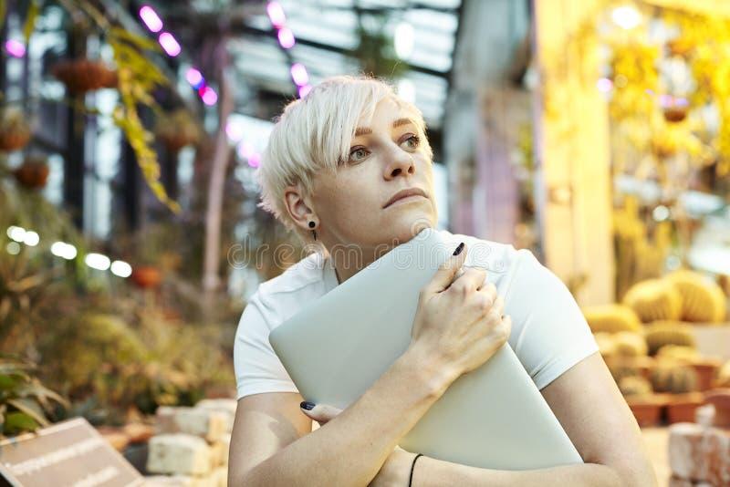 Mulher bonita do moderno que senta-se no parque ou no jardim botânico, olhar pensativo, pensando sobre coisas Guardando o portáti imagem de stock royalty free