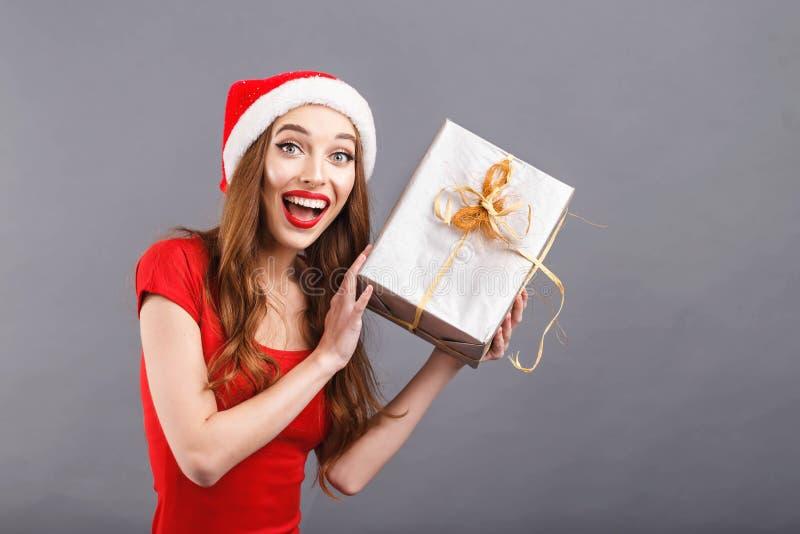 Mulher bonita do Natal que veste o presente de Santa Hat Shakes A imagem de stock