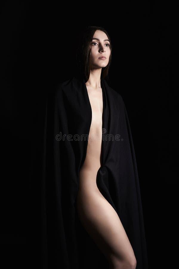 Mulher bonita do nude na matéria têxtil preta fotos de stock