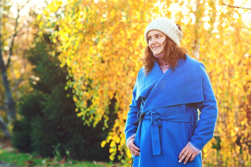 Mulher bonita do outono ao ar livre Forma da mulher Jovem mulher vestida no revestimento azul e no chapéu morno, andando no parqu fotos de stock royalty free