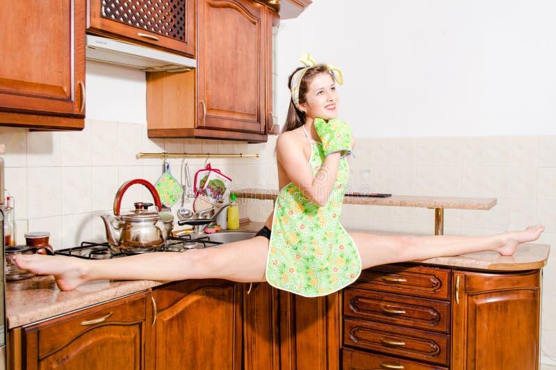 Mulher bonita do pinup que faz separações na cozinha imagens de stock