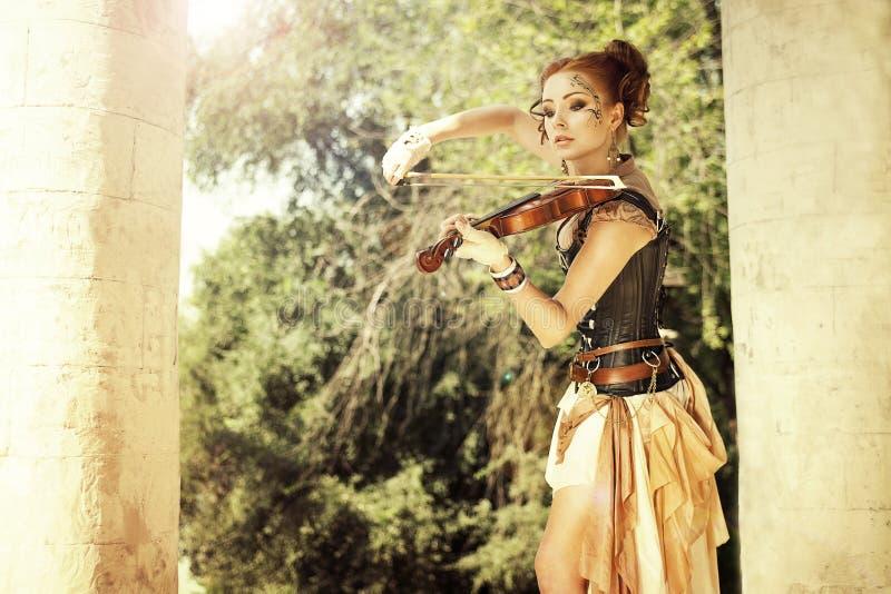 Mulher bonita do redhair com arte corporal em sua cara que joga no vio foto de stock
