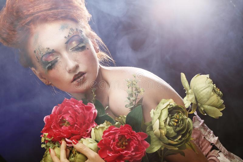 Mulher bonita do redhair que guarda flores fotos de stock