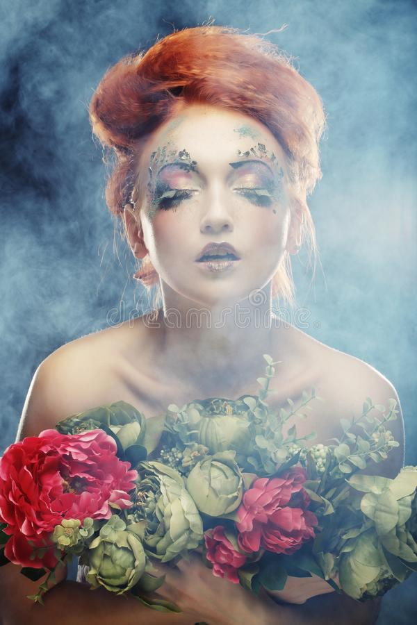 Mulher bonita do redhair que guarda flores fotos de stock royalty free