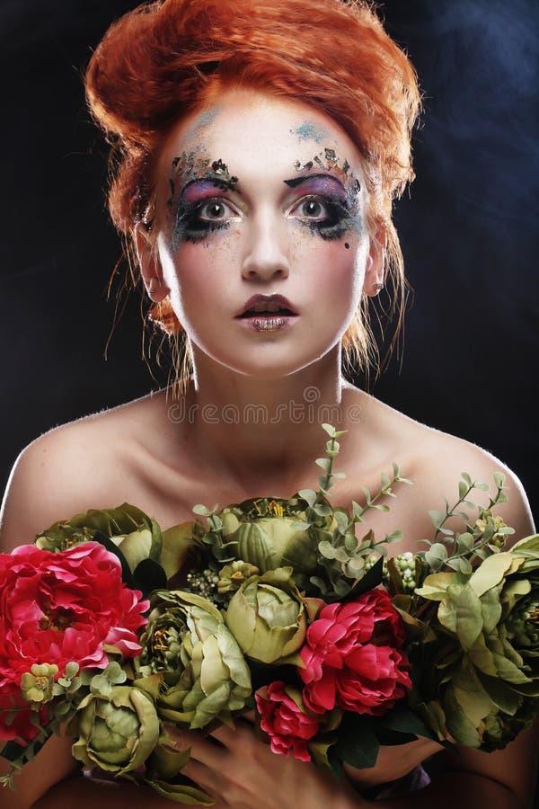 Mulher bonita do redhair que guarda flores foto de stock