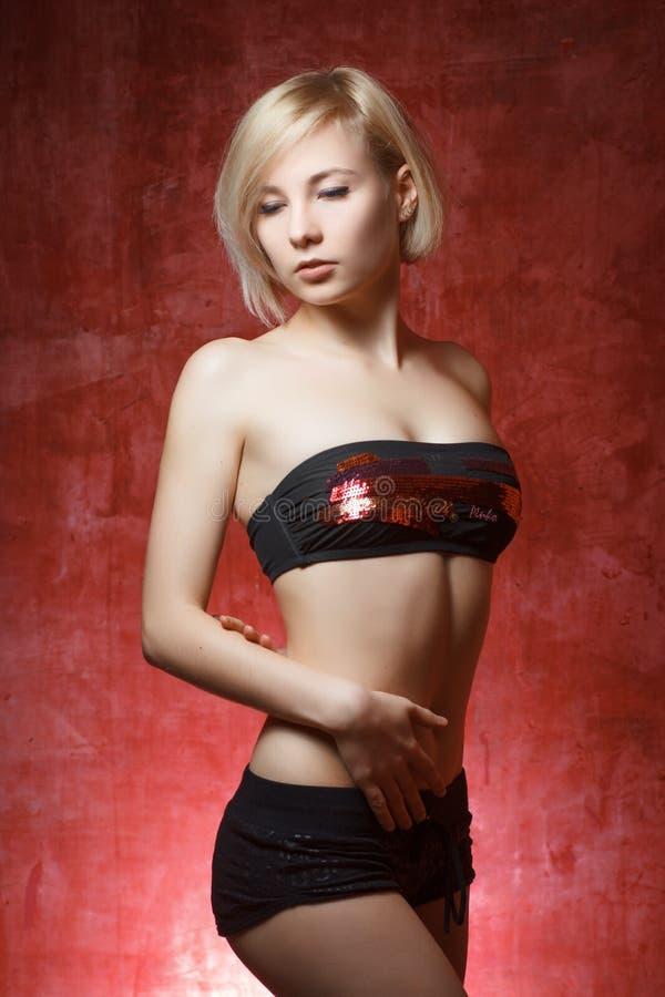 Mulher bonita do retrato no short na parede do grunge fotografia de stock royalty free