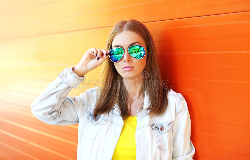 Mulher bonita do retrato nos óculos de sol sobre a laranja colorida foto de stock