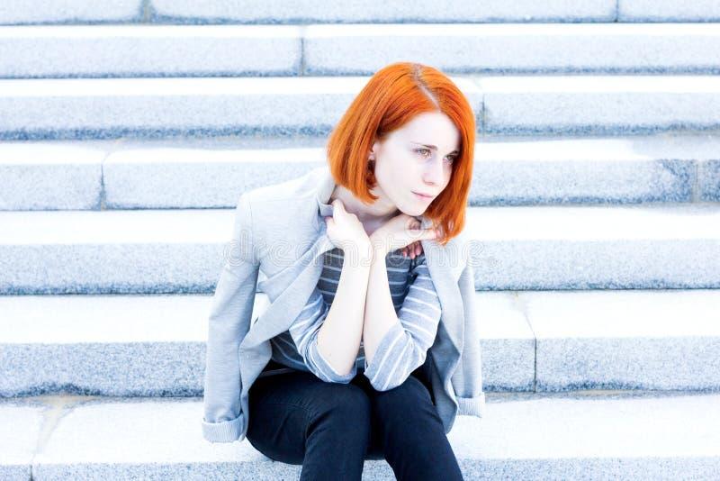 Mulher bonita do ruivo com um revestimento que senta-se nas escadas com um olhar pensativo fotos de stock