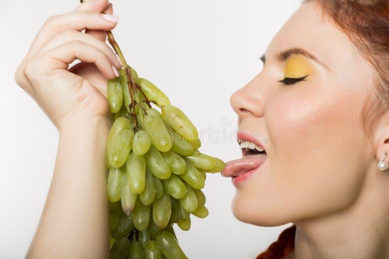 A mulher bonita do ruivo lambe uvas Conceito de comer saudável foto de stock