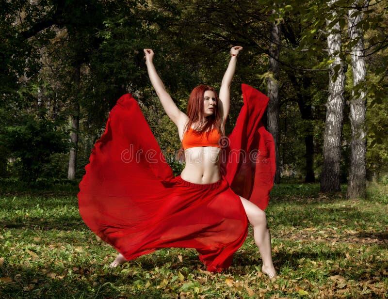 Mulher bonita do ruivo na dança vermelha do vestido em uma floresta do outono imagens de stock