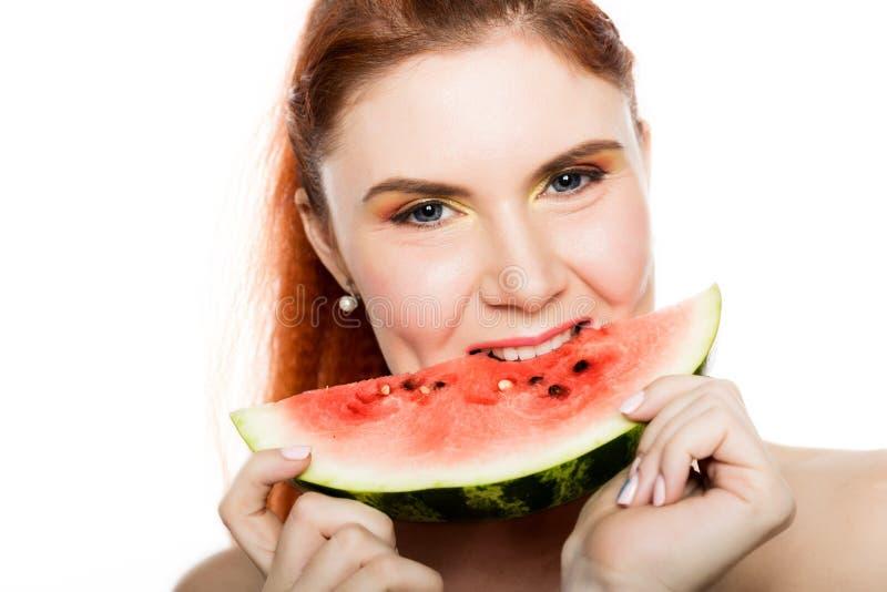 Mulher bonita do ruivo do nude que come uma fatia de melancia Conceito de comer saudável imagens de stock royalty free