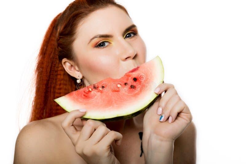 Mulher bonita do ruivo do nude que come uma fatia de melancia Conceito de comer saudável foto de stock