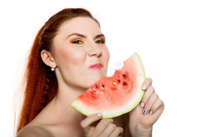 Mulher bonita do ruivo do nude que come uma fatia de melancia Conceito de comer saudável imagem de stock