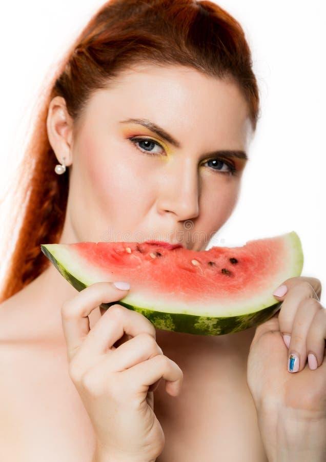 Mulher bonita do ruivo do nude que come uma fatia de melancia Conceito de comer saudável fotos de stock