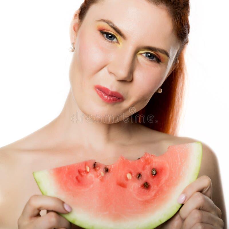 Mulher bonita do ruivo do nude que come uma fatia de melancia Conceito de comer saudável imagens de stock