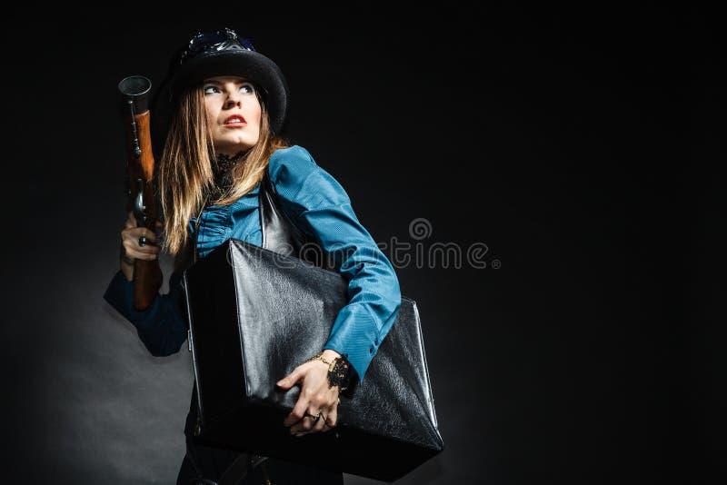 Mulher bonita do steampunk com saco e arma no preto fotografia de stock royalty free