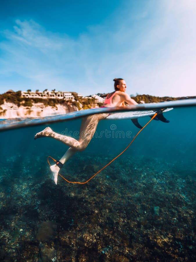 A mulher bonita do surfista relaxa com prancha Surfgirl no oceano fotografia de stock