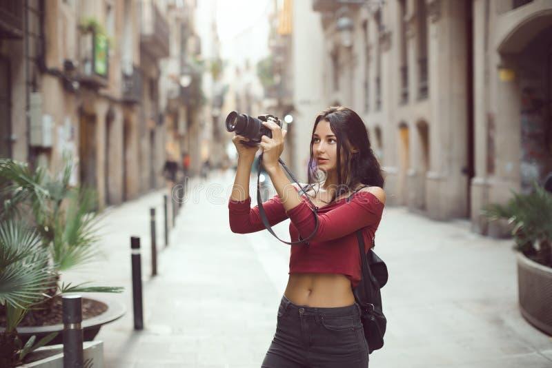 Mulher bonita do turista que toma uma imagem exterior na rua da cidade pela câmara digital foto de stock royalty free