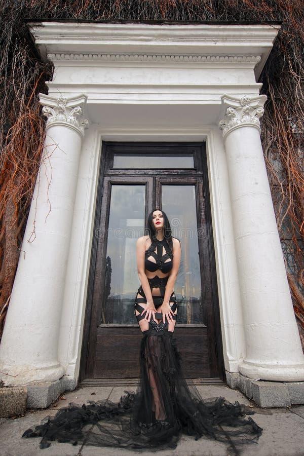 Mulher bonita do vampiro perto da porta do castelo velho imagem de stock royalty free