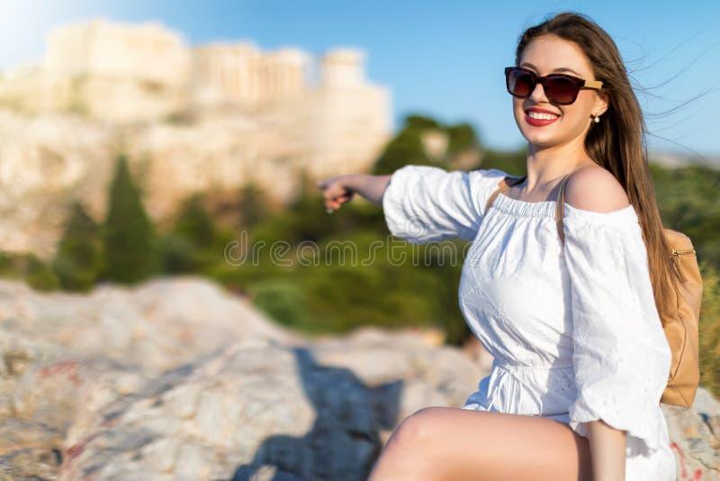 A mulher bonita do viajante da cidade aponta à acrópole de Atenas, Grécia imagens de stock royalty free