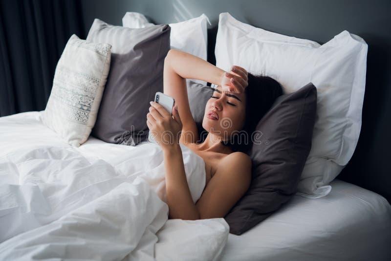 Mulher bonita doente que encontra-se na cama com febre alta Frio, gripe, febre e enxaqueca com um termômetro e um telefone foto de stock royalty free