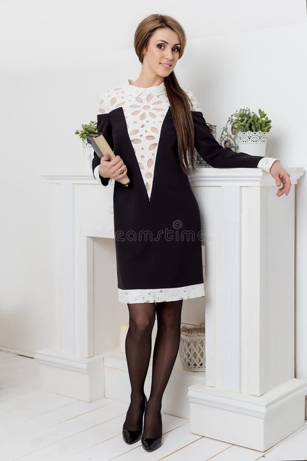 A mulher bonita dos beznes das mostras da moça anuncia o estilo do negócio do catálogo da roupa no estúdio claro brilhante imagens de stock royalty free
