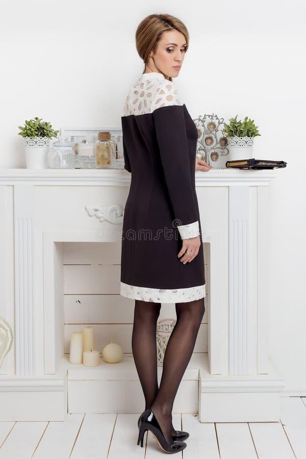 A mulher bonita dos beznes das mostras da moça anuncia o estilo do negócio do catálogo da roupa no estúdio claro brilhante imagem de stock