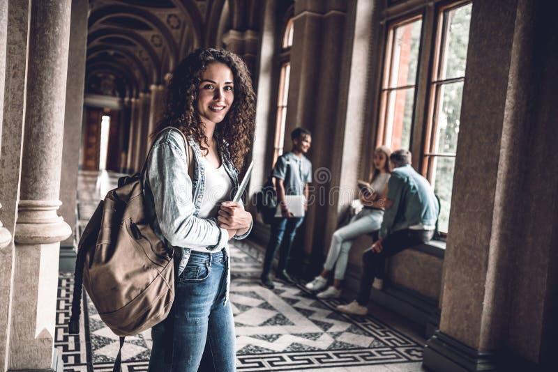 Mulher bonita e atrativa na universidade Posição nova do estudante fêmea no salão da universidade e vista da câmera fotografia de stock royalty free