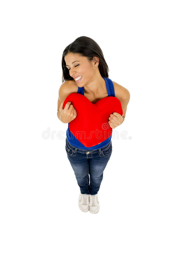Mulher bonita e feliz nova que mantém o sorriso vermelho da forma do coração do coxim isolado no branco foto de stock royalty free